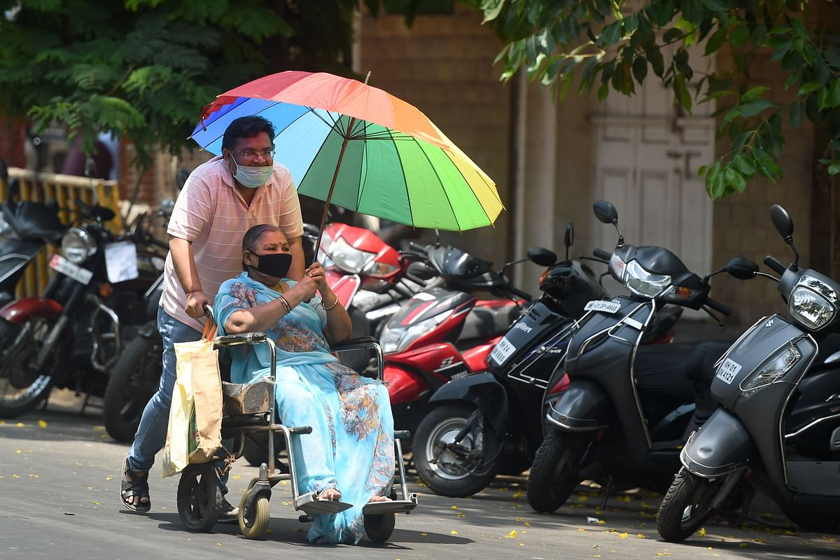 A man wearing mask carries pushes a woman on a wheelchair during a government-imposed nationwide lockdown as a preventive measure against the spread of the COVID-19 coronavirus in Mumbai