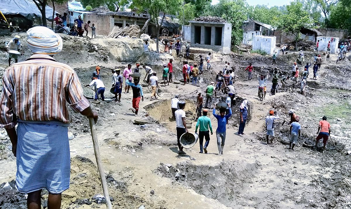 Migrant workers digging a pond under the MGNREGA scheme in their home state