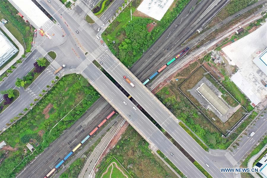 """Aerial photo shows a China-Europe freight train, also the """"China Post"""" CR Express 1st block train, running under a bridge in Chongqing Municipality, southwest China, April 3, 2020. Initiated in 2011, the China-Europe rail transport service is considered a significant part of the Belt and Road Initiative to boost trade between China and countries participating in the program. Amid the coronavirus pandemic, the service remained a reliable transportation channel as air, sea and road transportation have been severely affected. The freight trains have also been playing a crucial role in helping with the fight against the pandemic in Europe, sending massive quantities of medical supplies such as face masks and goggles."""