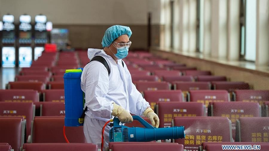 A staff member disinfects a waiting room of Beijing Railway Station