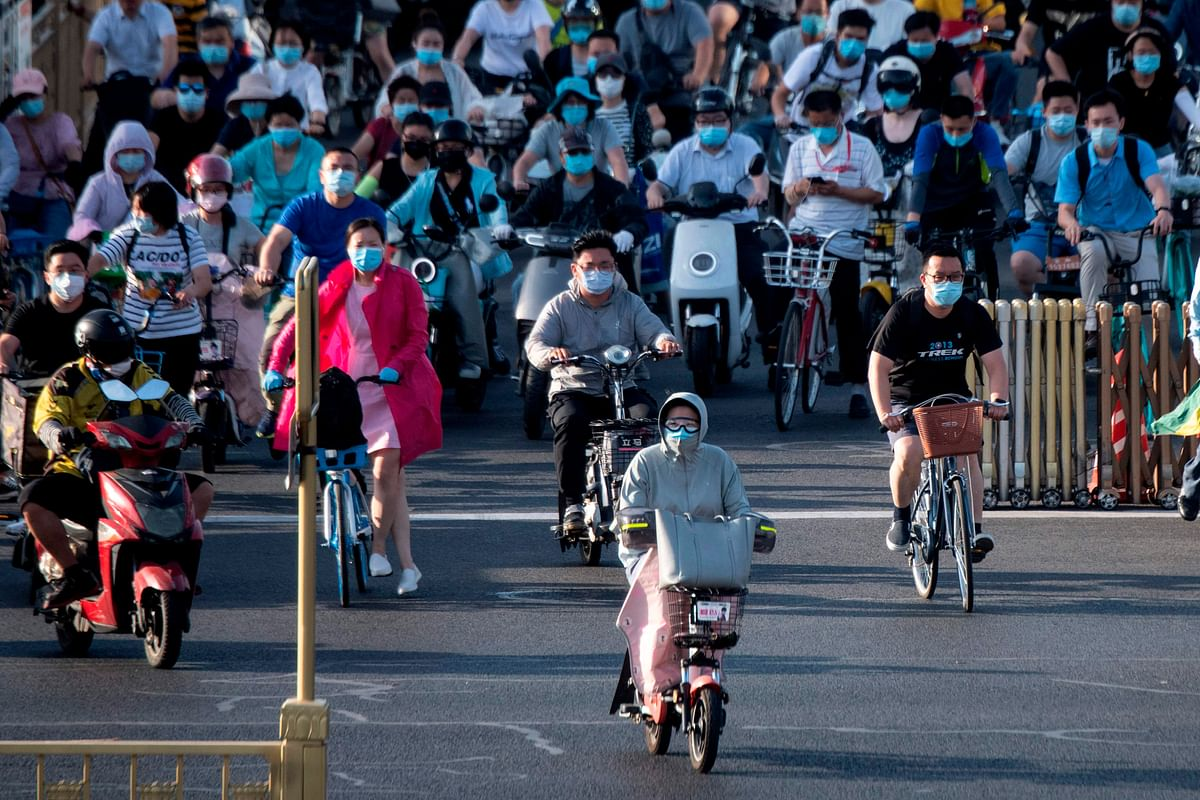 People with face masks ride their  motocycles during rush hour in Beijing.