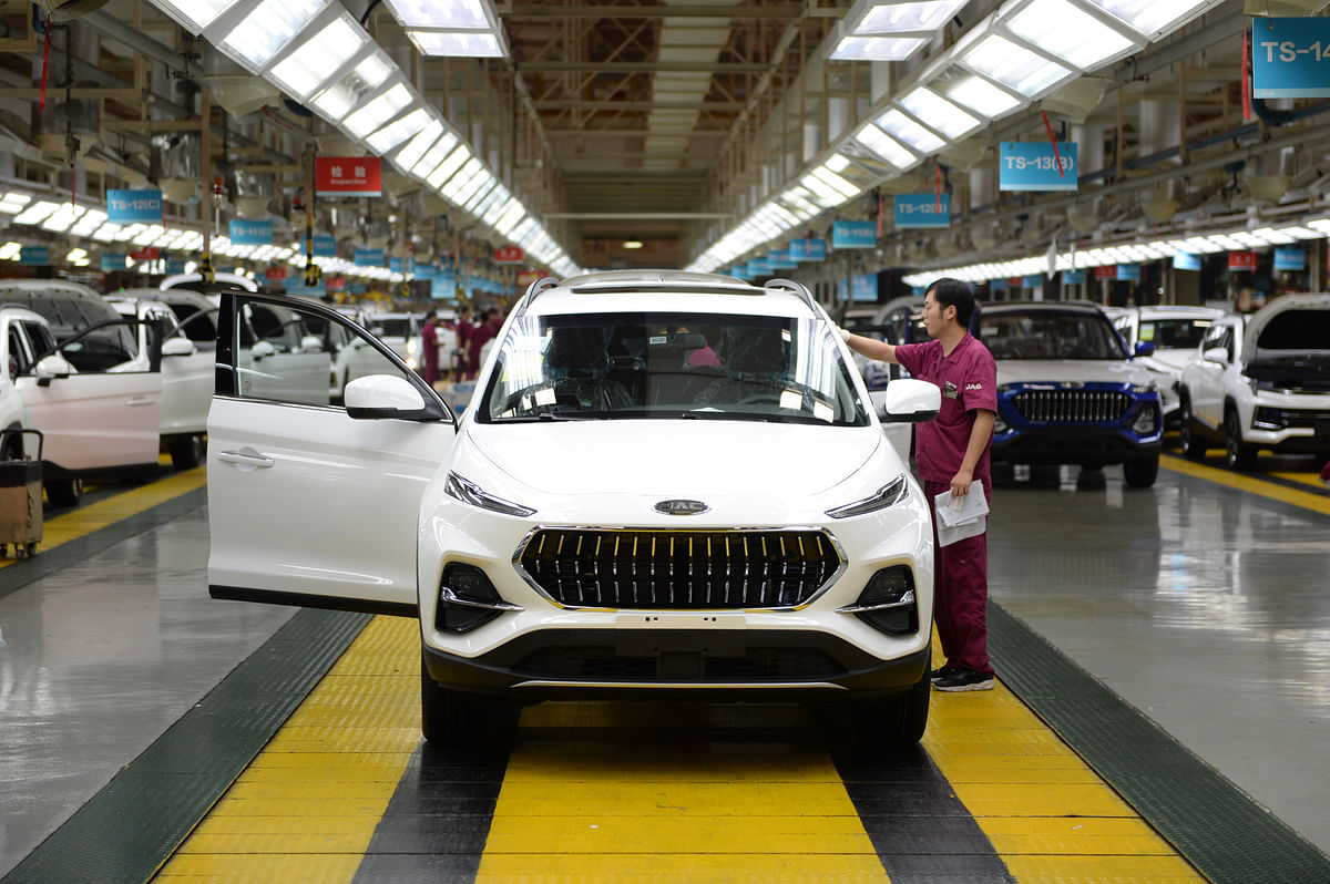 A worker exams a newly assembled car at the passenger vehicle assembly plant of Anhui Jianghuai Automobile Group Corp., Ltd. in Hefei, east China's Anhui Province, June 19, 2020.
