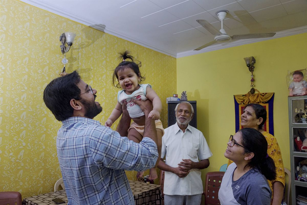 AIIMS Senior Resident Doctor Meet Minare (33) plays with his 10-month-old child as his wife Dr. Ranjuna (R), mother Anita (2R) and father Ramesh look on, at their Anand Vihar residence in New Delhi, Thursday, June 18, 2020. All five members of the family came out COVID-19 positive and have since been on a recovery path. Being an anaesthetist, Minare has to attend to patients, without a PPE suit, who are in intense pain and often without the knowledge whether they are COVID-19 negative or not. His wife, who is a gynecologist, goes through the same concerns as she cannot deny treatment to any patient, even if they are positive.