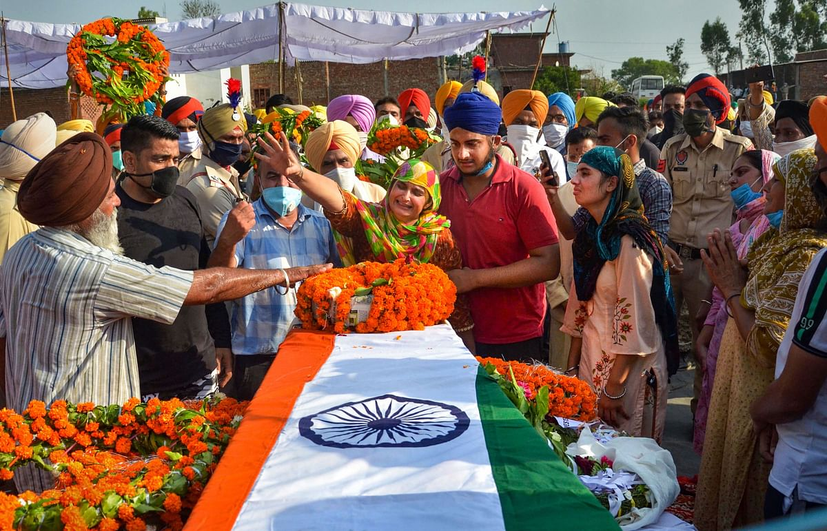 Family members of martyr Naib Subedar Satnam Singh mourn near his mortal remains during his last rites, at his native village Vhoj Raj in Gurdaspur district, Thursday, June 18, 2020. Singh was among the twenty Indian Army soldiers who were martyred during a face-off with Chinese troops in Ladakhs Galwan Valley