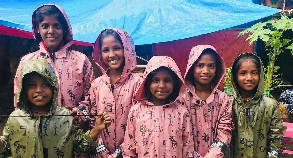 Street children pose with their new raincoats provided to them by The Raincoat Project