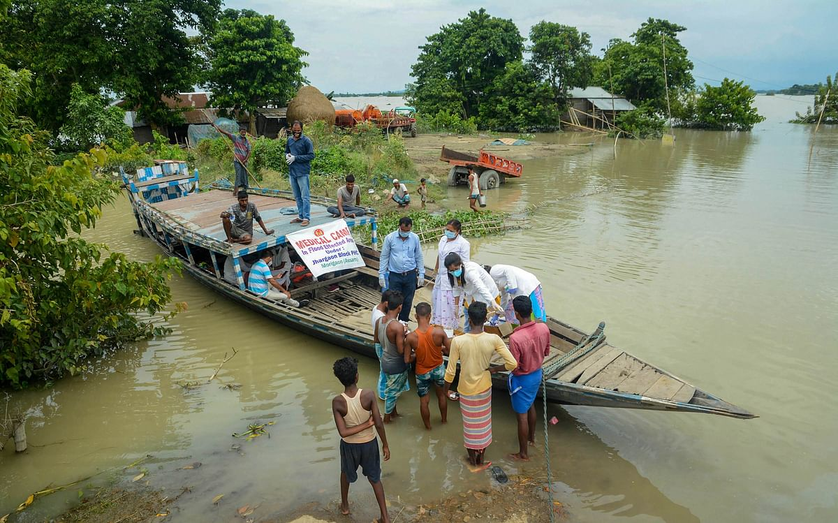 A team of medics provide medicines to the flood-affected people in Morigaon district of Assam, Thursday, July 23, 2020