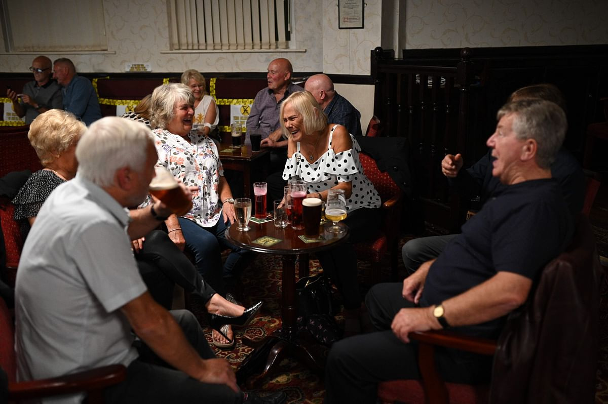 People enjoy a drink with yellow tape on the seats aiding social distancing inside the Burnley Miners Working Mens Social Club in Burnley, northwest England, on July 4, 2020, as restrictions are further eased during the novel coronavirus COVID-19 pandemic