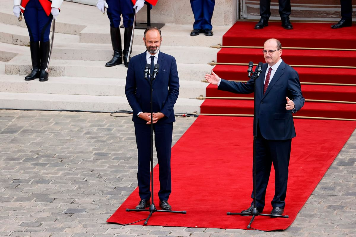 Former French Prime Minister Edouard Philippe (L) listens to newly-appointed Prime Minister Jean Castex as he addresses media in the courtyard of the Matignon Hotel during the handover ceremony in Paris on July 3, 2020.