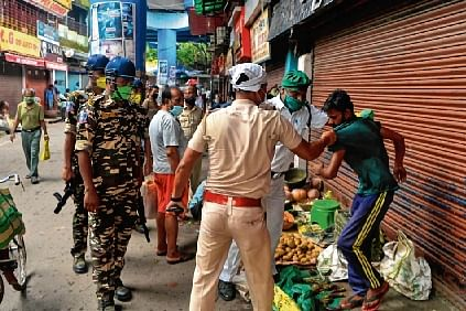 Policemen force vegetable vendors to clear a roadside market as a preventive measure against the spread of the virus in Siliguri on Sunday. A lockdown has been imposed in the area until July 29.