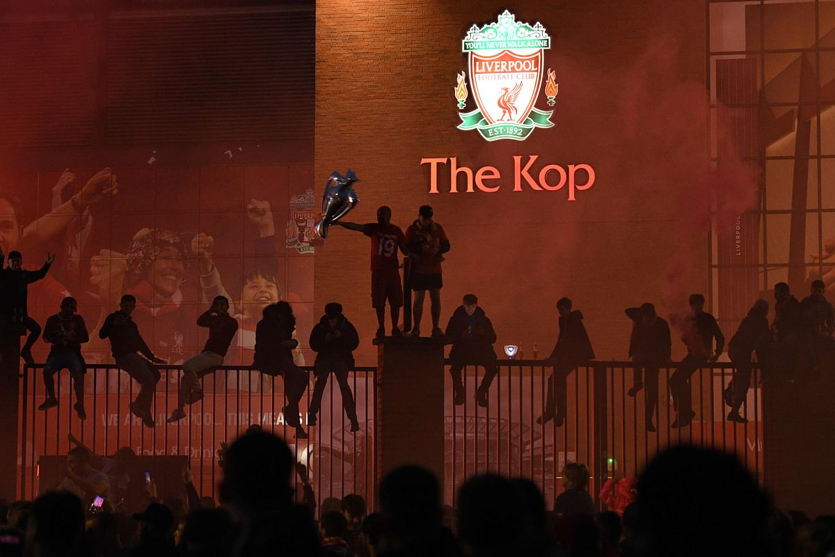 Liverpool fans celebrate outside Anfield in Liverpool, north west England on July 22, 2020 after Liverpools final home English Premier League football match of the season against Chelsea after which the team was presented with the Premier League trophy