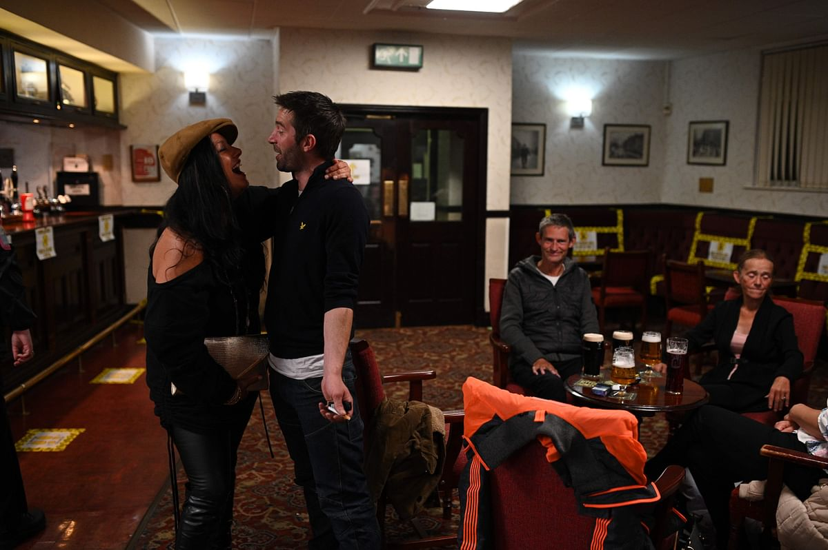 People enjoy a drink inside the Burnley Miners Working Mens Social Club in Burnley, northwest England, on July 4, 2020, as restrictions are further eased during the novel coronavirus COVID-19 pandemic.