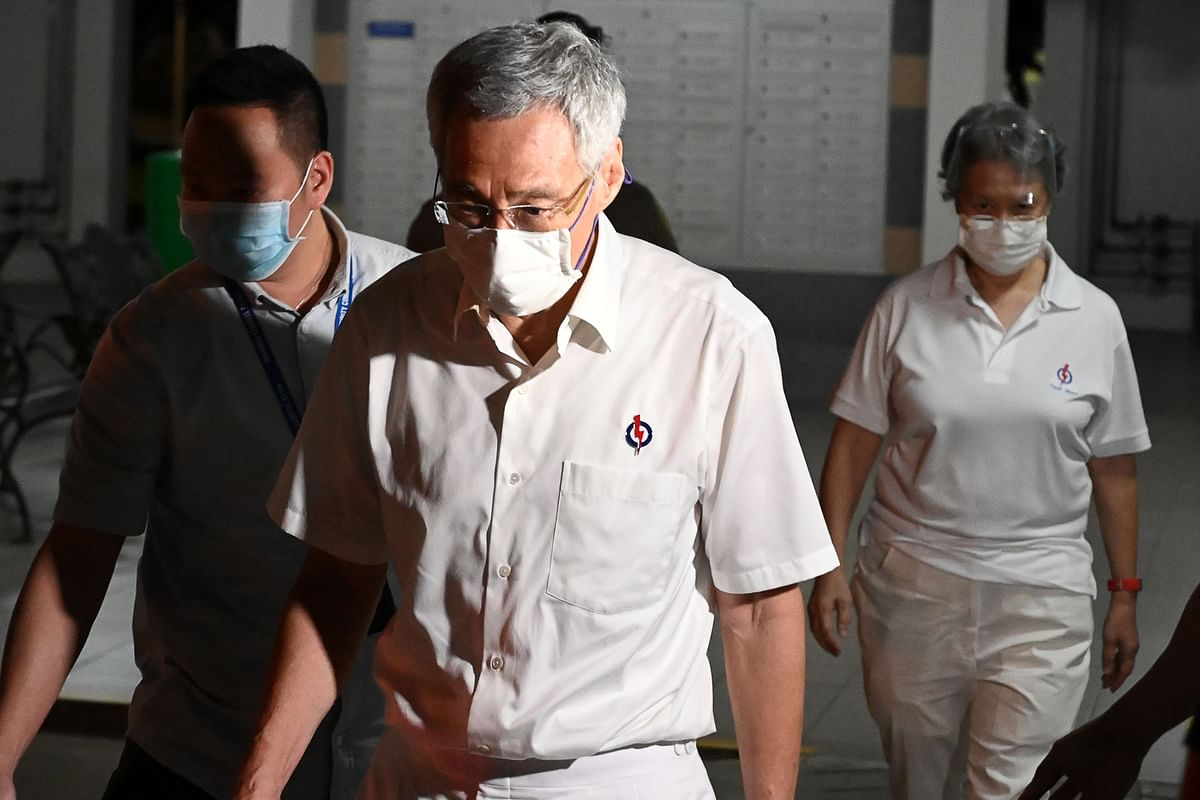 Singapore's Prime Minister and secretary-general of the ruling Peoples Action Party Lee Hsien Loong (C) and his wife Ho Ching (R) leave the party's office after delivering the speech live on Facebook to citizens during the counting of votes of the general election in Singapore