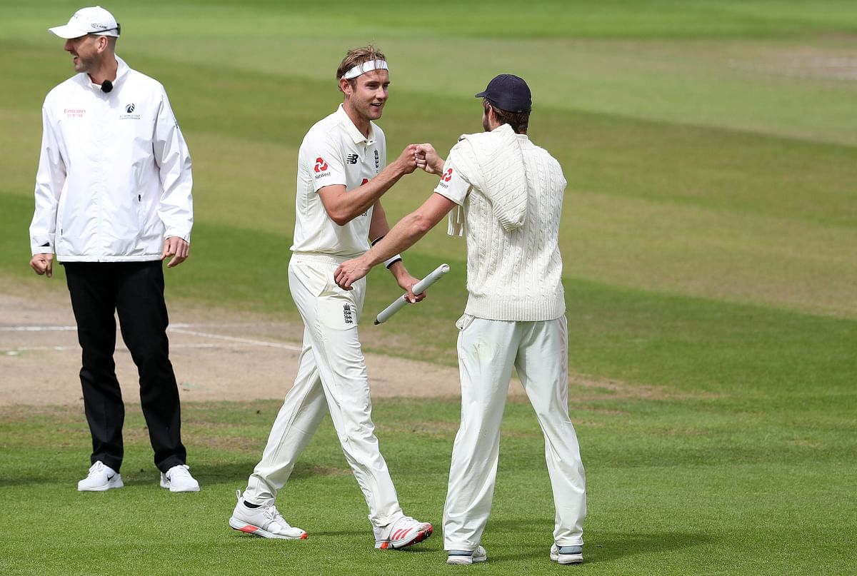 Chris Woakes (C) and England's Stuart Broad react after winning the third Test cricket match between England and the West Indies at Old Trafford in Manchester, northwest England