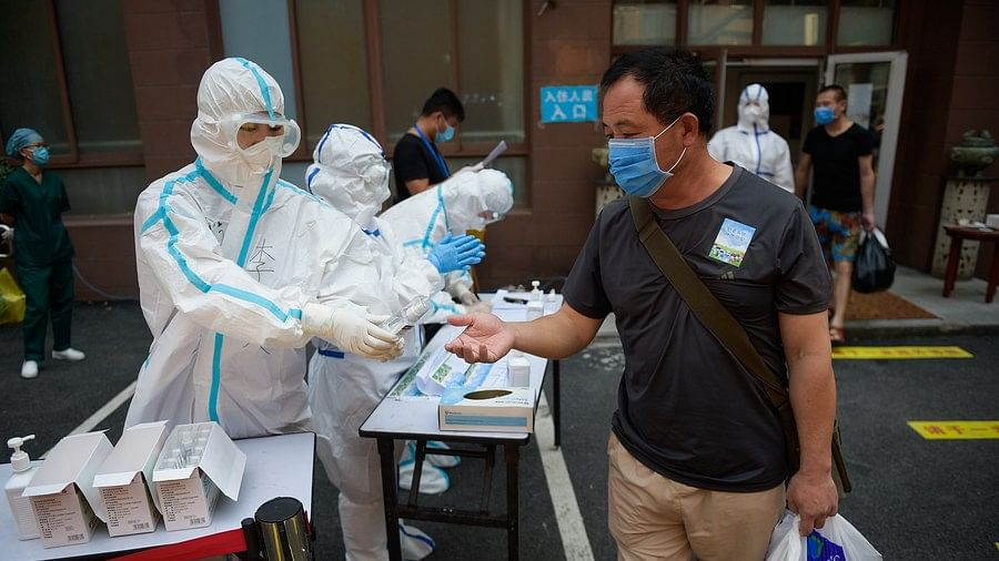 A man who finished quarantine receives hand sanitizer from a staff member at a designated facility in Beijing, capital of China, July 7, 2020