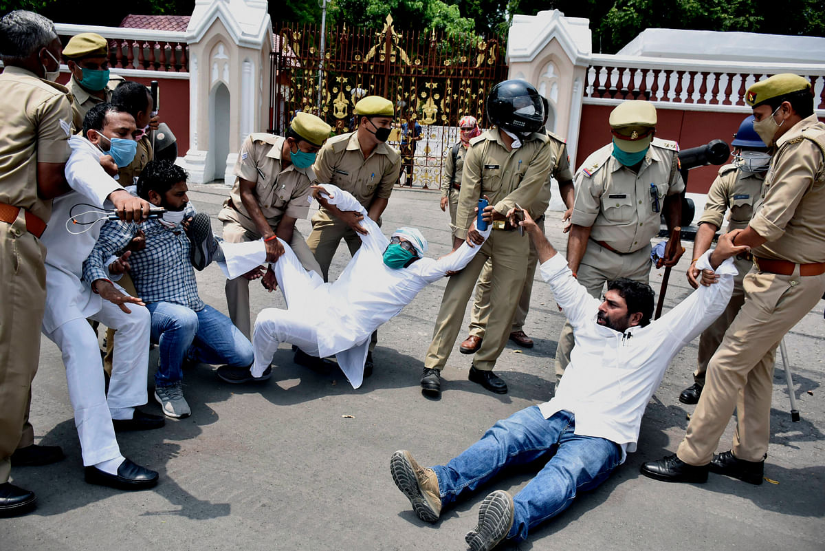 Congress supporters being detained by Police personnel as they protest against the BJP infront of the Raj Bhavan in Lucknow on Monday.