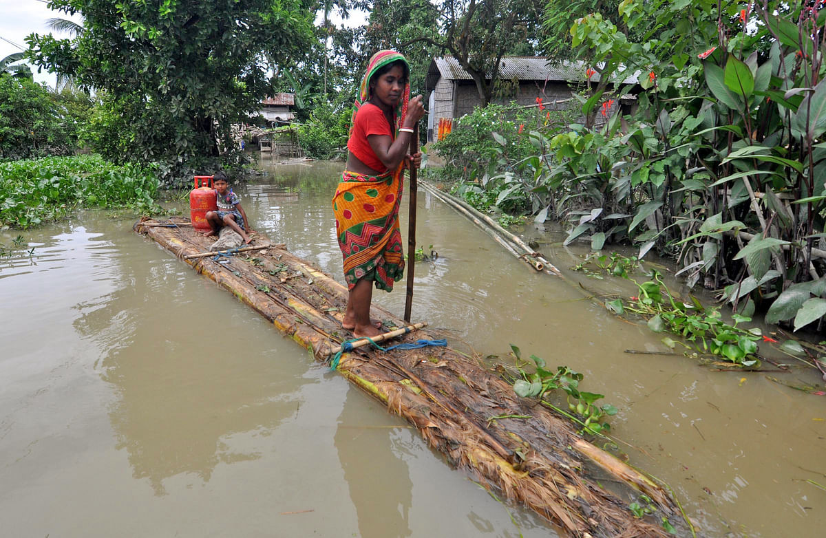 A woman use a banana raft to cross floodwater at Murkata village in Assam's Morigaon district on Thursday