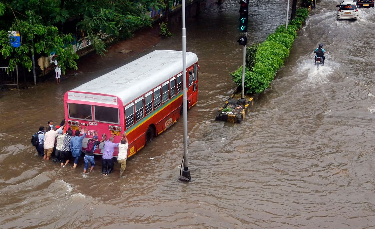 Passengers push a bus after it broke down on a flooded road following heavy monsoon rain, at Wadala in Mumbai on Thursday.
