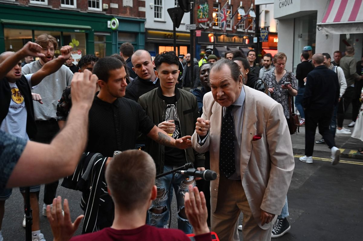 A man (C) drinks a shot of whisky in the street in the Soho area of London on July 4, 2020, as restrictions are further eased during the novel coronavirus COVID-19 pandemic.