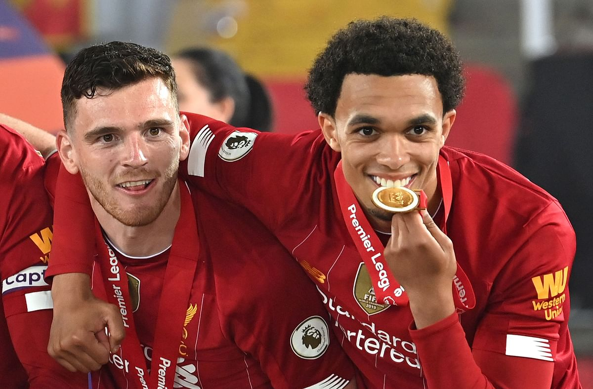 (L-R) Liverpools Scottish defender Andrew Robertson and Liverpools English defender Trent Alexander-Arnold pose during the Premier League trophy presentation following the English Premier League football match between Liverpool and Chelsea at Anfield in Liverpool, north west England