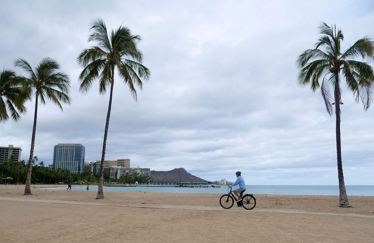 A cyclist rides along an empty Waikiki Beach as Hurricane Douglas veers northward sparing Oahu from a direct hit, in Honolulu, Hawaii.