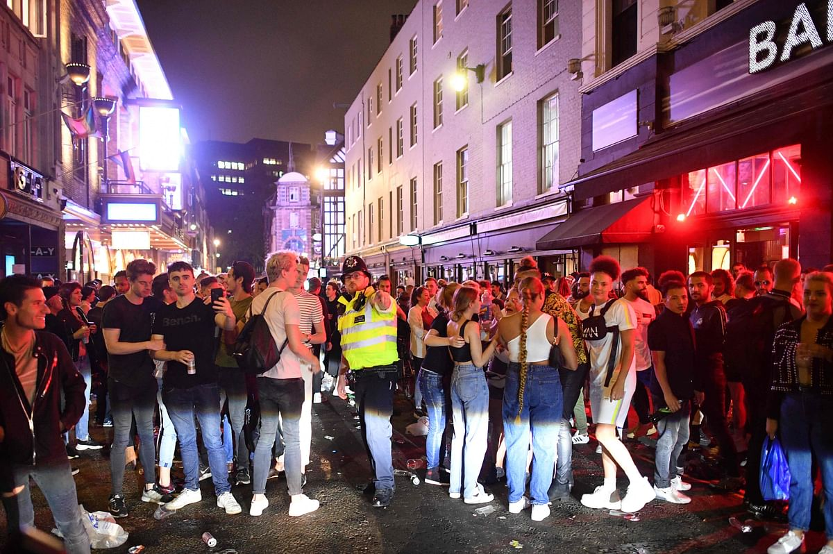 A police officer tries to tell revellers filling the street outside bars in the Soho area of London on July 4, 2020, that the road has been reopened to car traffic as restrictions are further eased during the novel coronavirus COVID-19 pandemic.