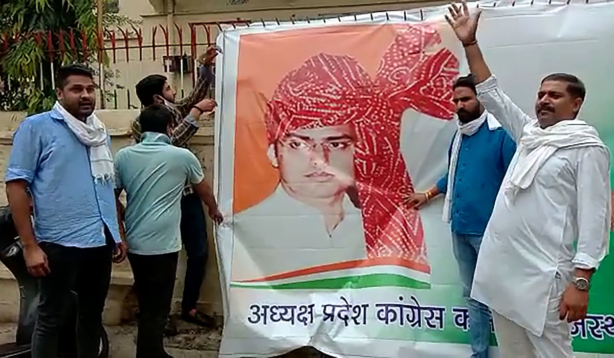 NSUI workers pasting a banner of Sachin Pilot outside PCC office following its removal