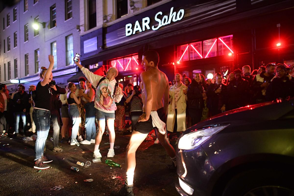 A car tries to drive along a street filled with revellers drinking in the Soho area of London on July 4, 2020, after the police re-opened the road at 2300 as restrictions are further eased during the novel coronavirus COVID-19 pandemic.