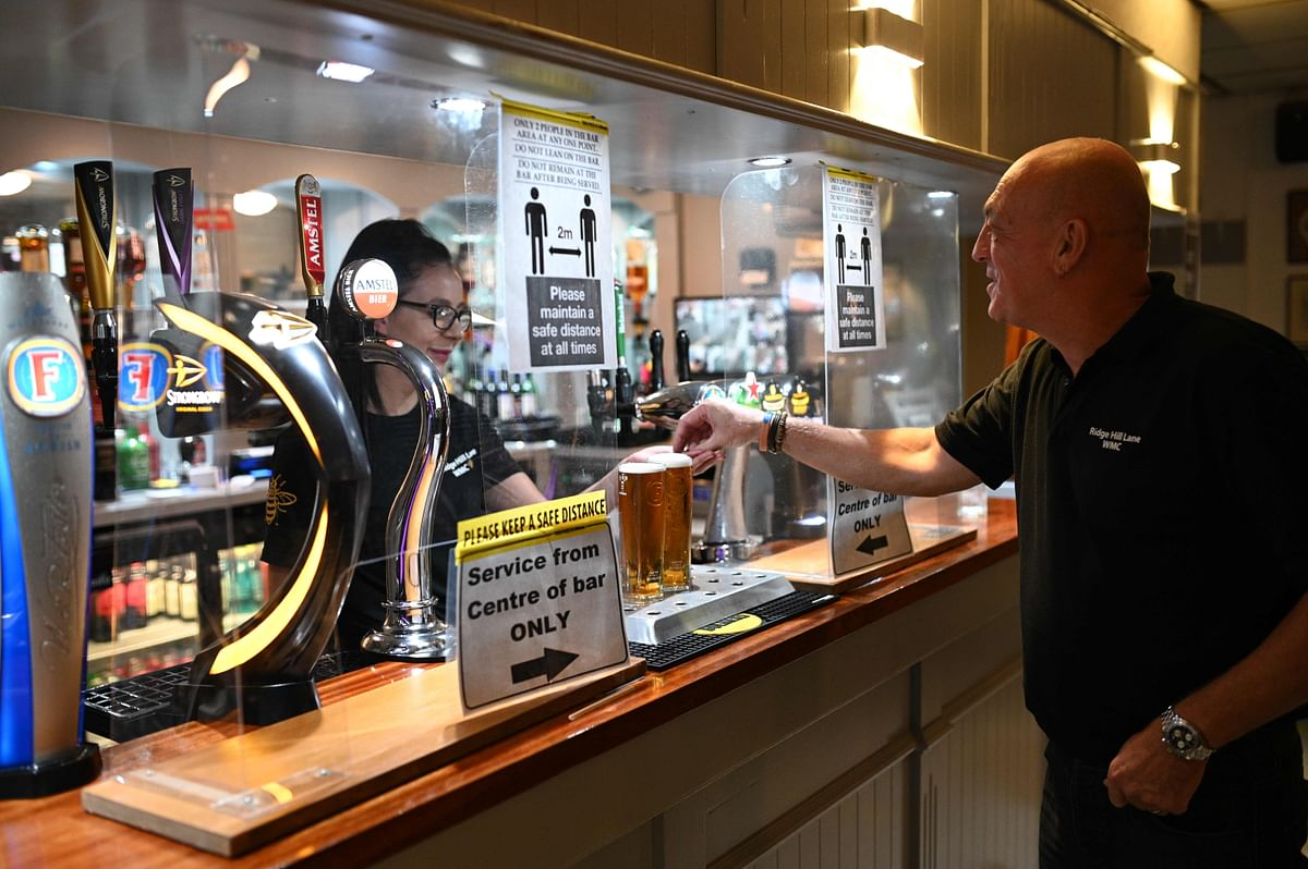 A man pays for drinks at a bar protected by a perspex screen with signs reminding members to socially distance inside the Ridge Hill Working Mens Club in Stalybridge, northwest England, on July 4, 2020, as restrictions are further eased during the novel coronavirus COVID-19 pandemic.