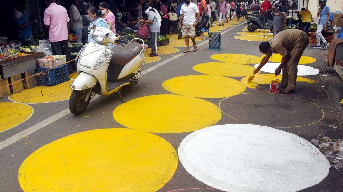 A BMC worker paints white and yellow marks for vendors with license and their customers to maintain social distancing in the wake of coronavirus pandemic at Grant Road Market, Mumbai