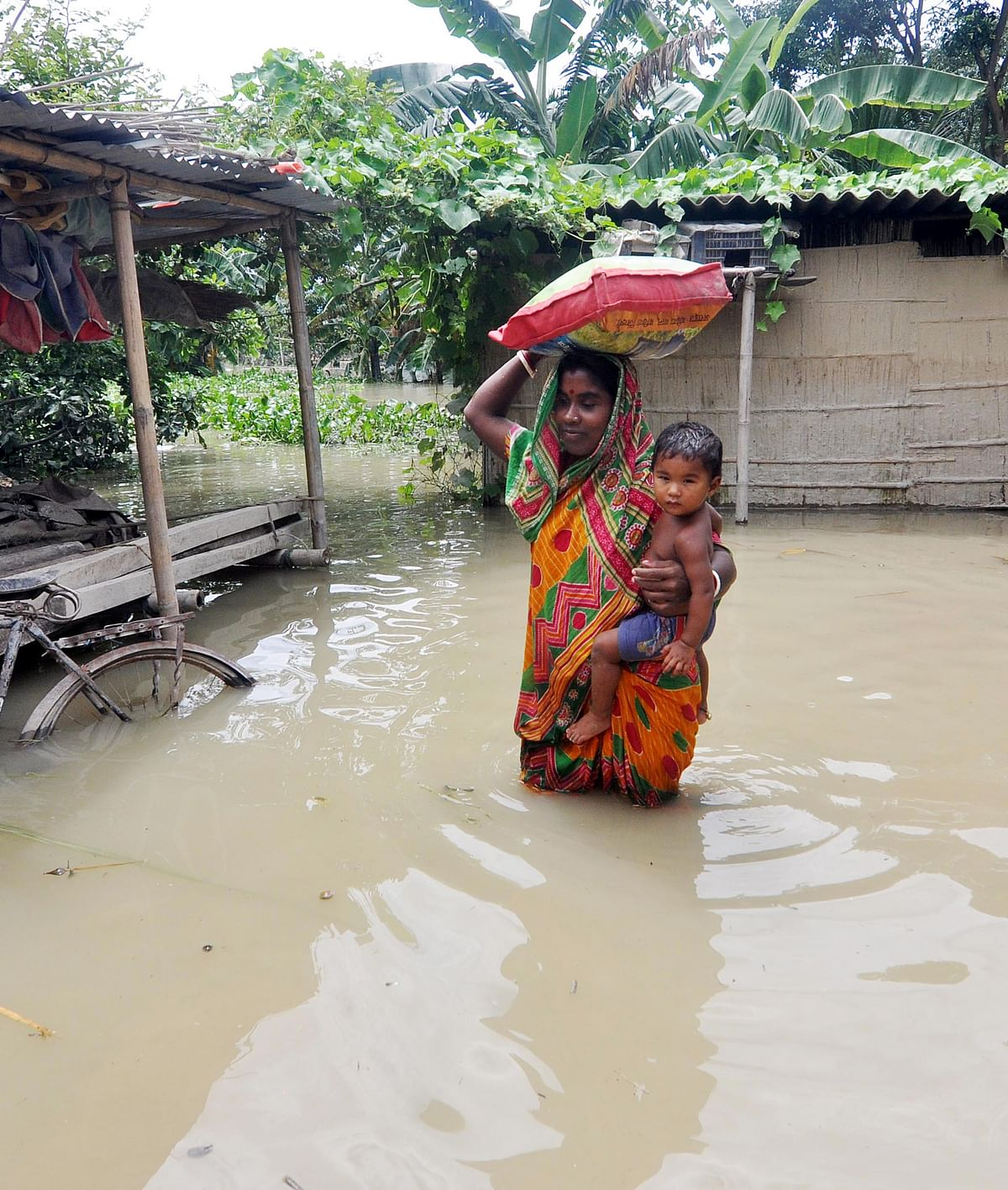 Assam, July 23 (ANI): A woman with her child stand in the flooded water of Murkata village in Morigaon district on Thursday.