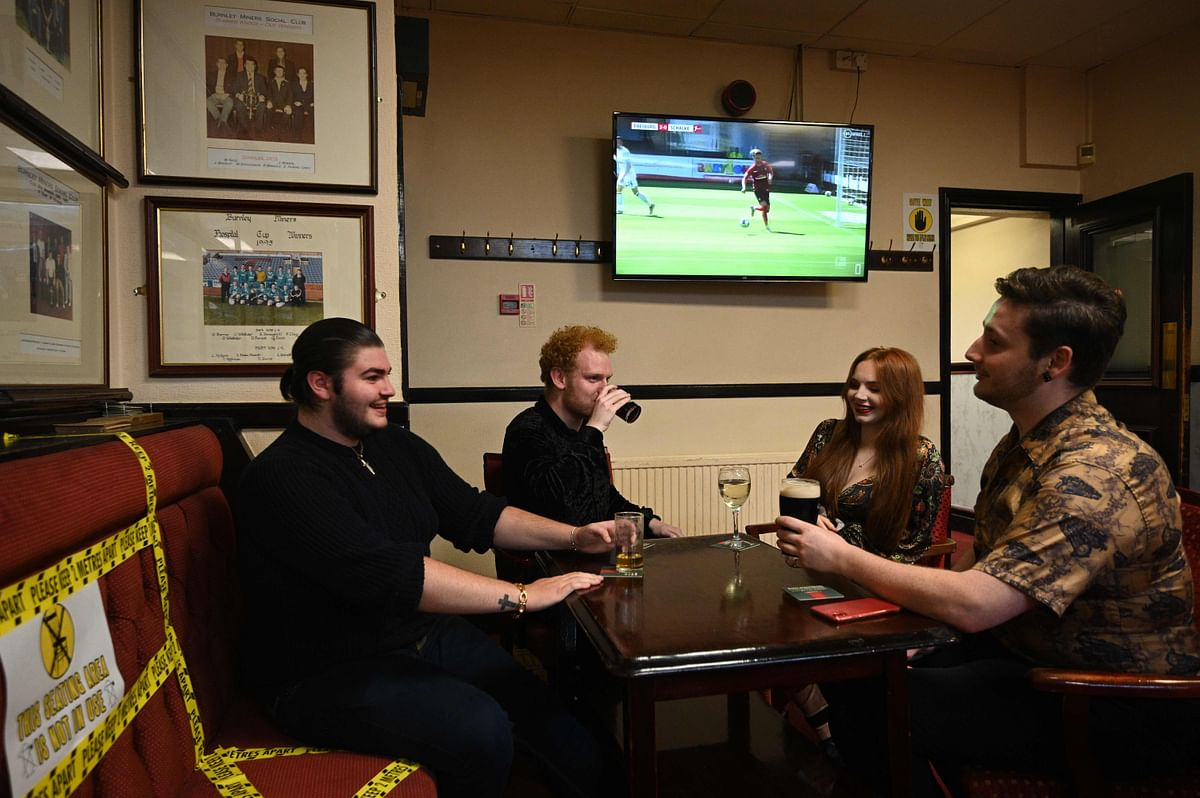 People enjoy a drink with yellow tape on the seats and floor aiding social distancing inside the Burnley Miners Working Mens Social Club in Burnley, northwest England, on July 4, 2020, as restrictions are further eased during the novel coronavirus COVID-19 pandemic.