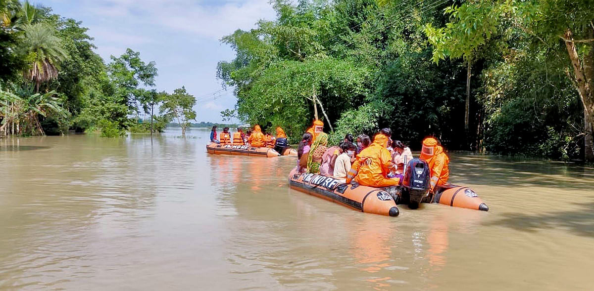 National Disaster Response Force (NDRF) personnel rescue people from a flood-affected village at Kamrup district, in Guwahati on Monday.