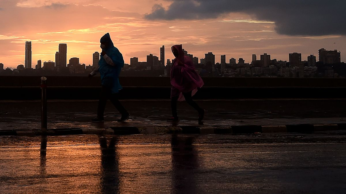 People walk at the sea front during rain showers in Mumbai on Tuesday.