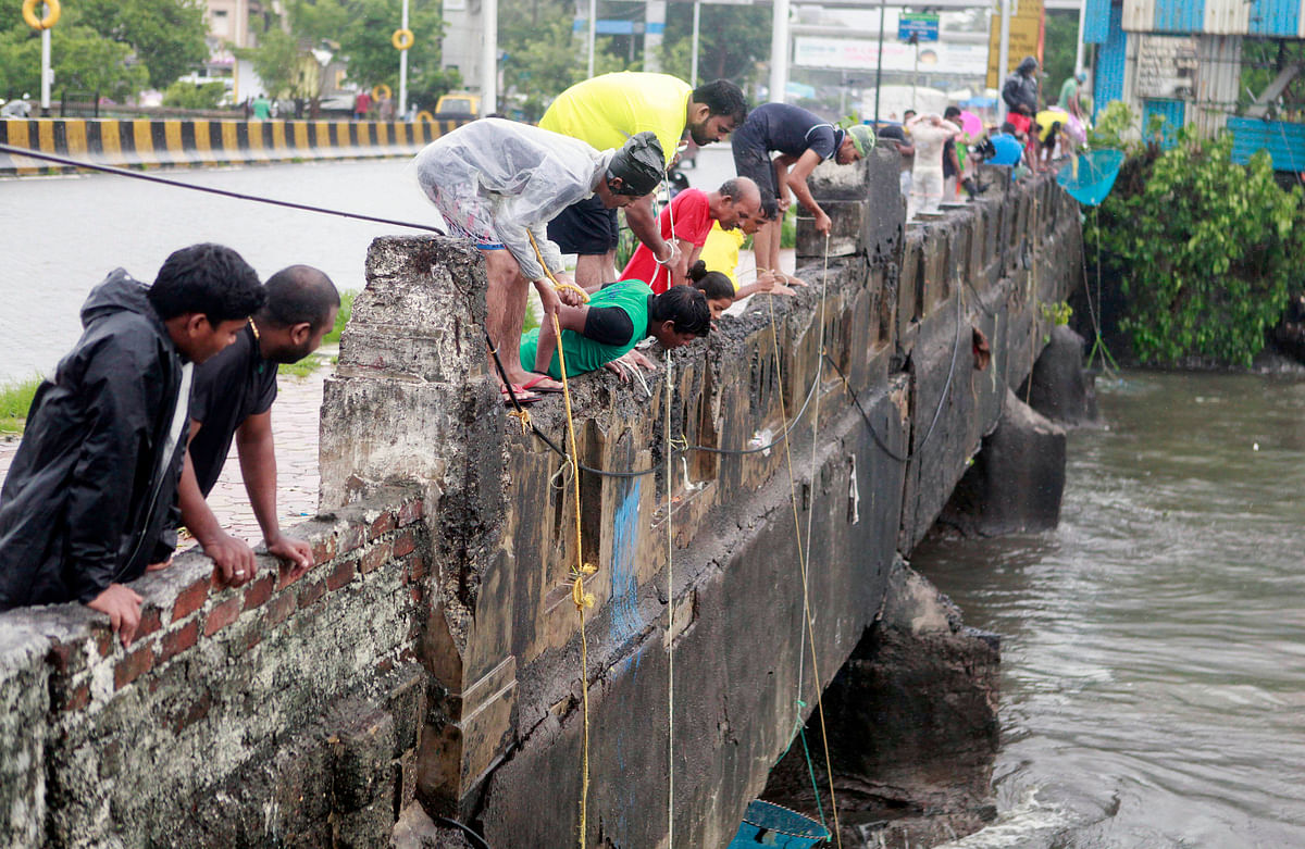 People fishing from bridge after heavy rainfall, at Mahim Creek in Mumbai on Sunday.