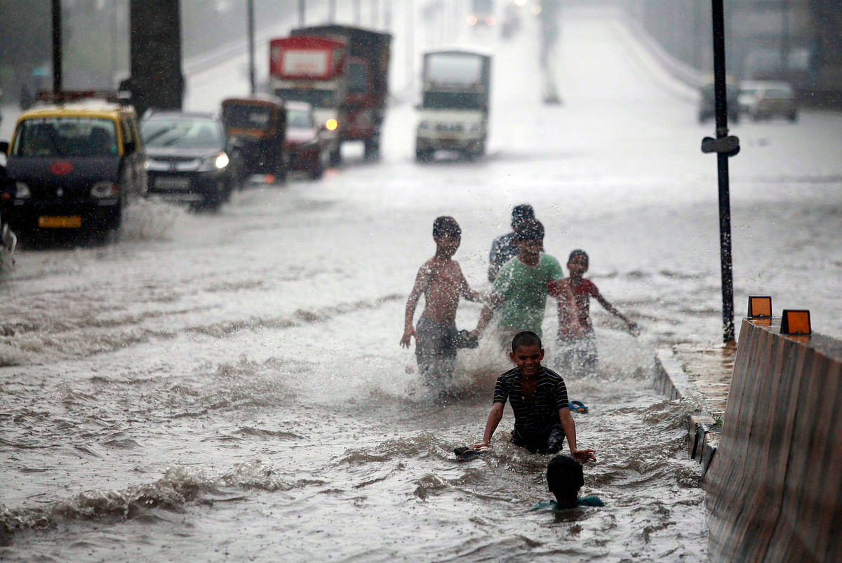 Children enjoying in water logging road after heavy rainfall, at Tilkanagar in Mumbai on Sunday.