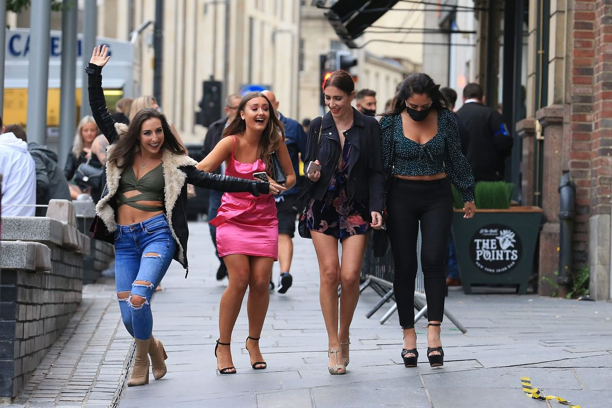 Women pose in the street on a night out in Newcastle, northern England on July 4, 2020, as restrictions are further eased during the novel coronavirus COVID-19 pandemic.