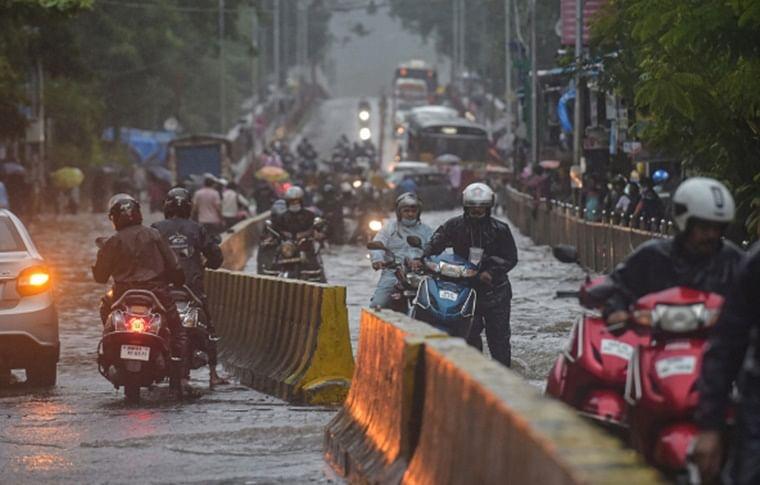 Commuters make way through a waterlogged road during rain, in Mumbai, Wednesday, Aug