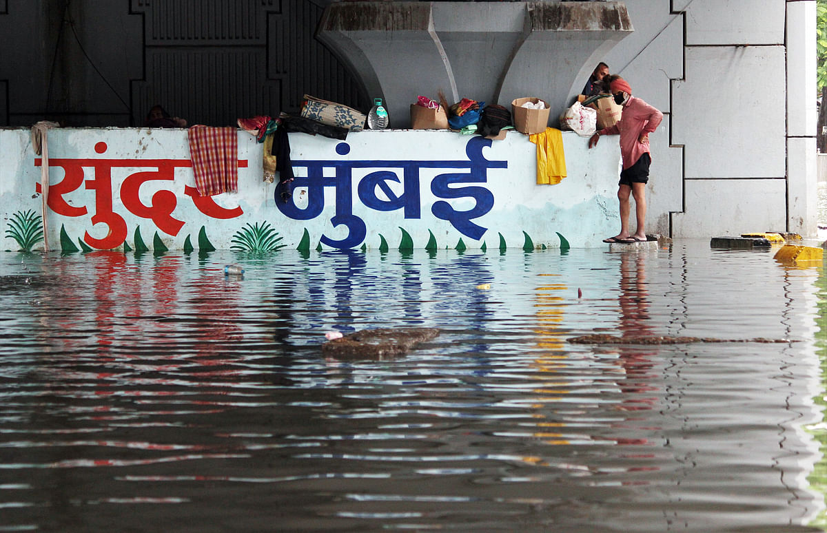 People stand on corners on a waterlogged road during rains