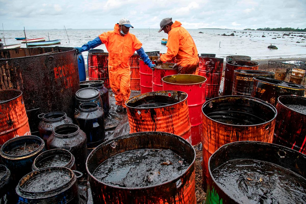 Workers collect leaked oil at the beach in Riviere des Creoles.