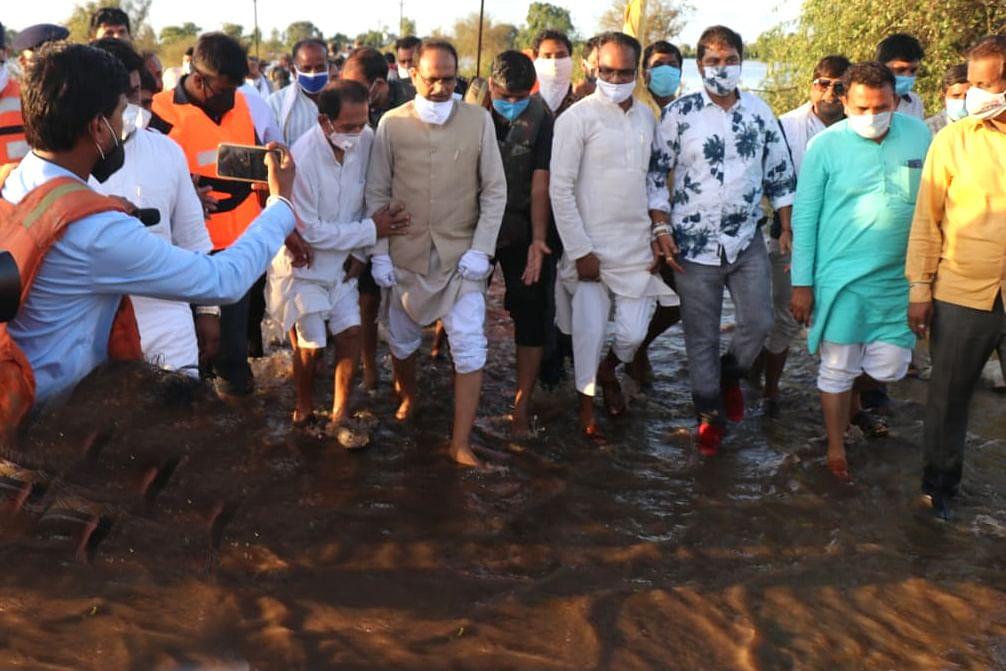 CM Shivraj Singh Chouhan walks through mud barefoot to reach flood-hit areas.