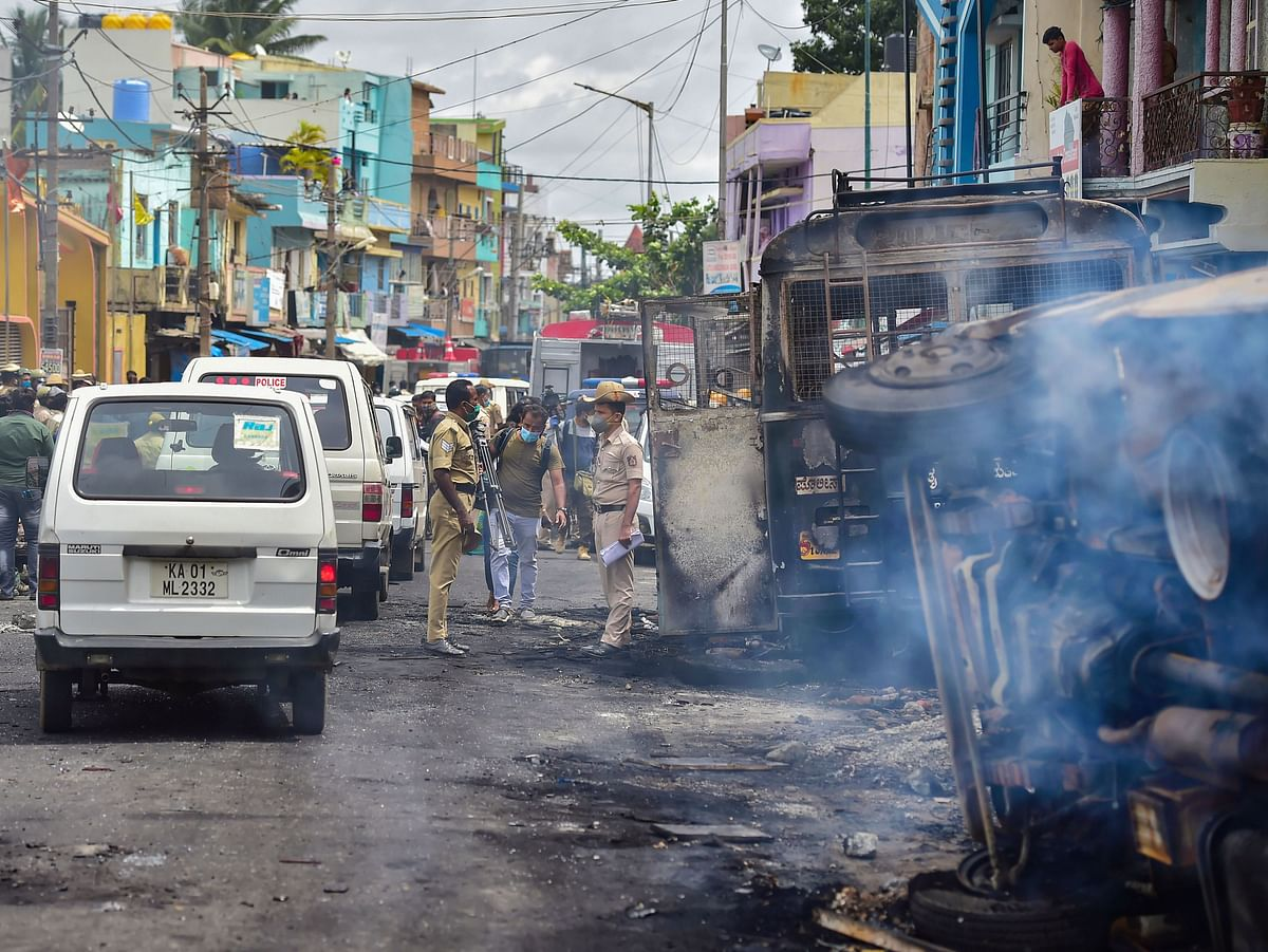 Police stand guard next to charred remains of vehicles vandalised by a mob over a social media post, allegedly by a relative of a Congress MLA, in Bengaluru, Wednesday, Aug. 12, 2020