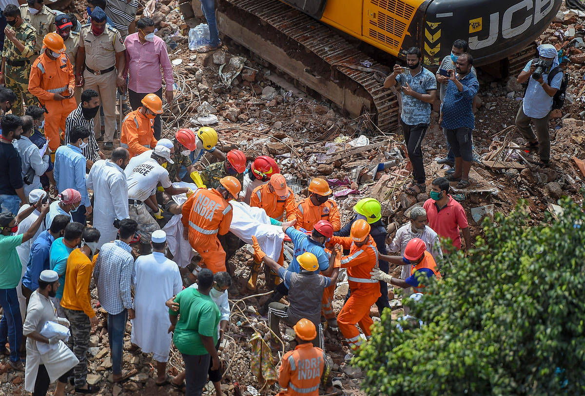 Workers carry a body recovered from the debris of a collapsed five-storey building in Mahad, Raigad, Tuesday