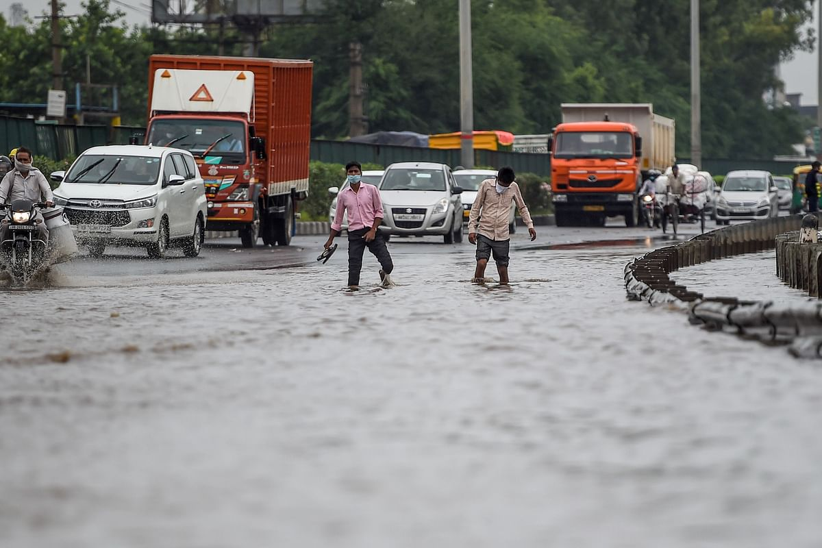 Vehicles and people wade on a flooded road following monsoon rainfall in Gurugram on August 20, 2020.