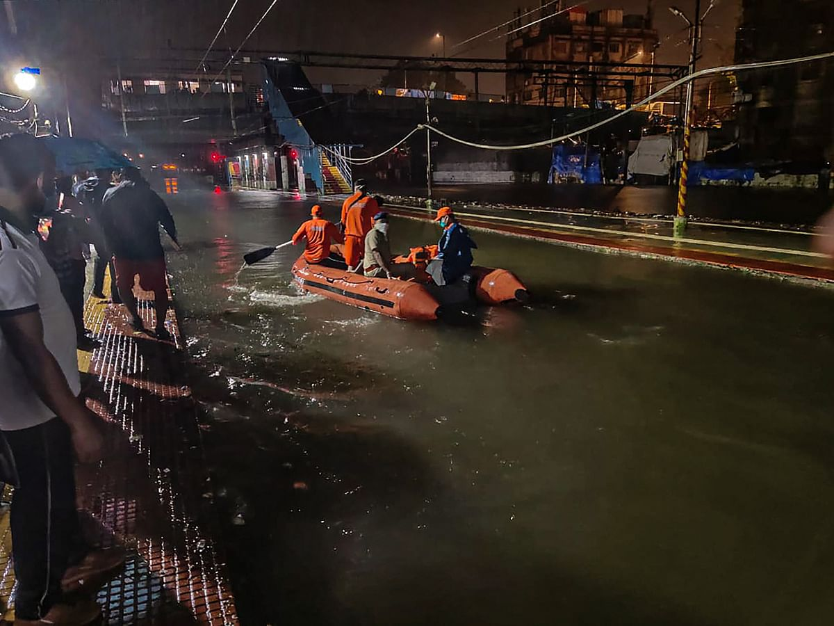 National Disaster Response Force (NDRF) personnel rescue passengers from a local train stranded between Masjid Bunder and Byculla stations on the Central line, during heavy rain, in Mumbai, Wednesday, Aug. 5