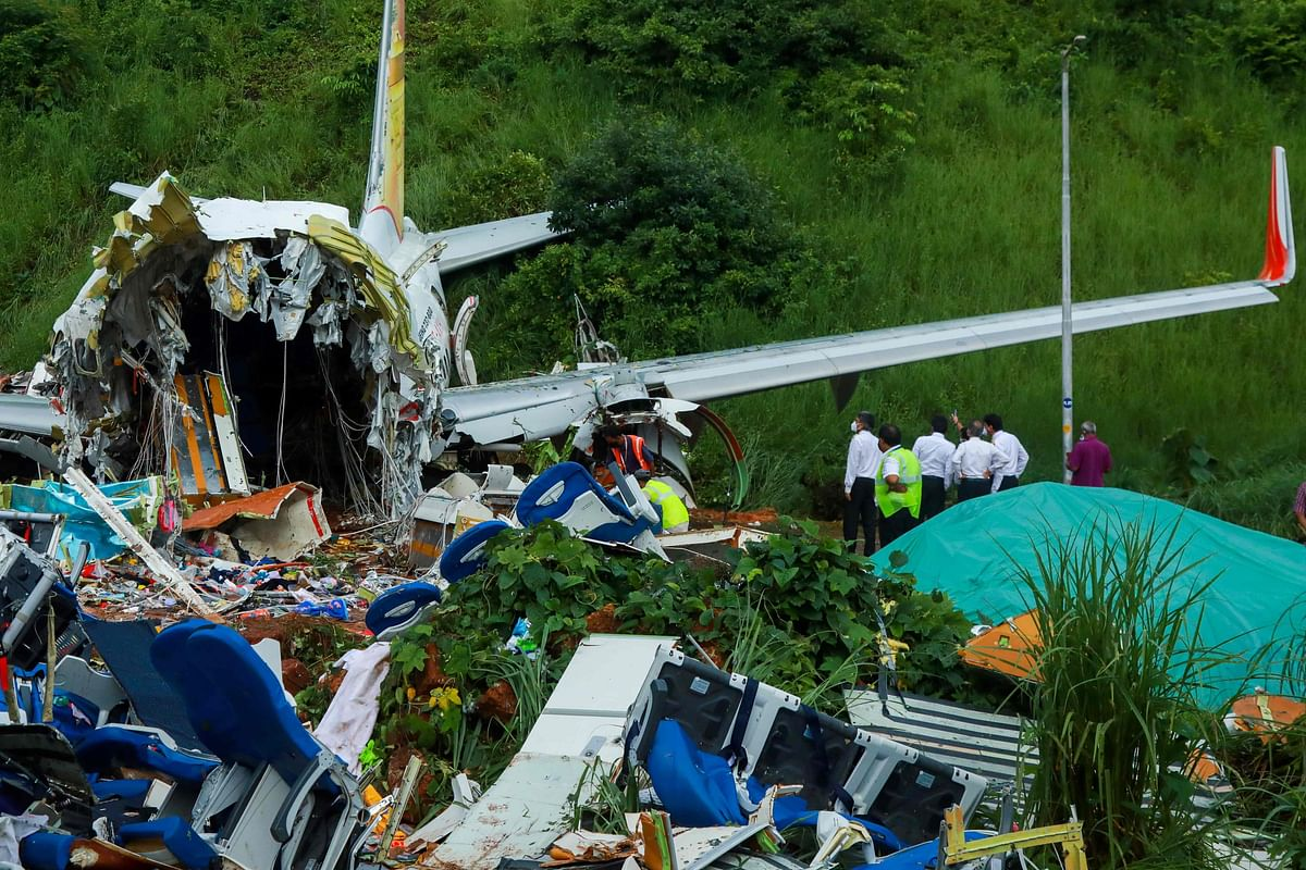 Officials inspect the wreckage of an Air India Express jet at Calicut International Airport in Karipur, Kerala, on August 8, 2020.