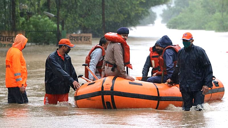 NDRF personnel rescue people after their houses submerged in floodwater in Hoshangabad on Sunday.