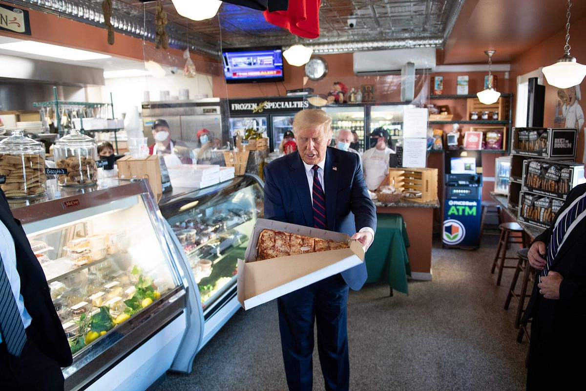 President Donald Trump takes a pizza break after campaign event.