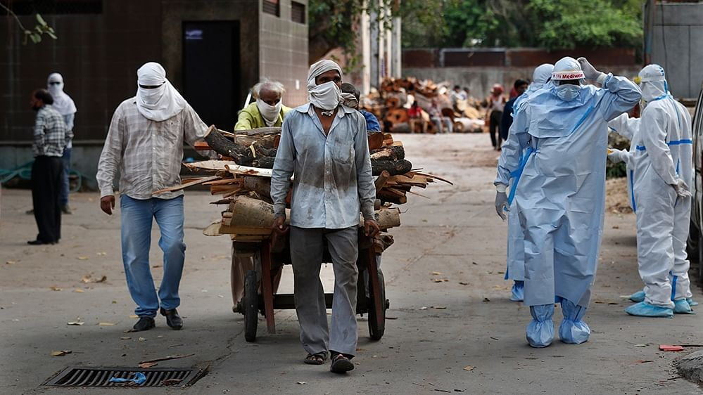 A file photo of workers bringing wood for the funerals of COVID-19 victims at a crematorium