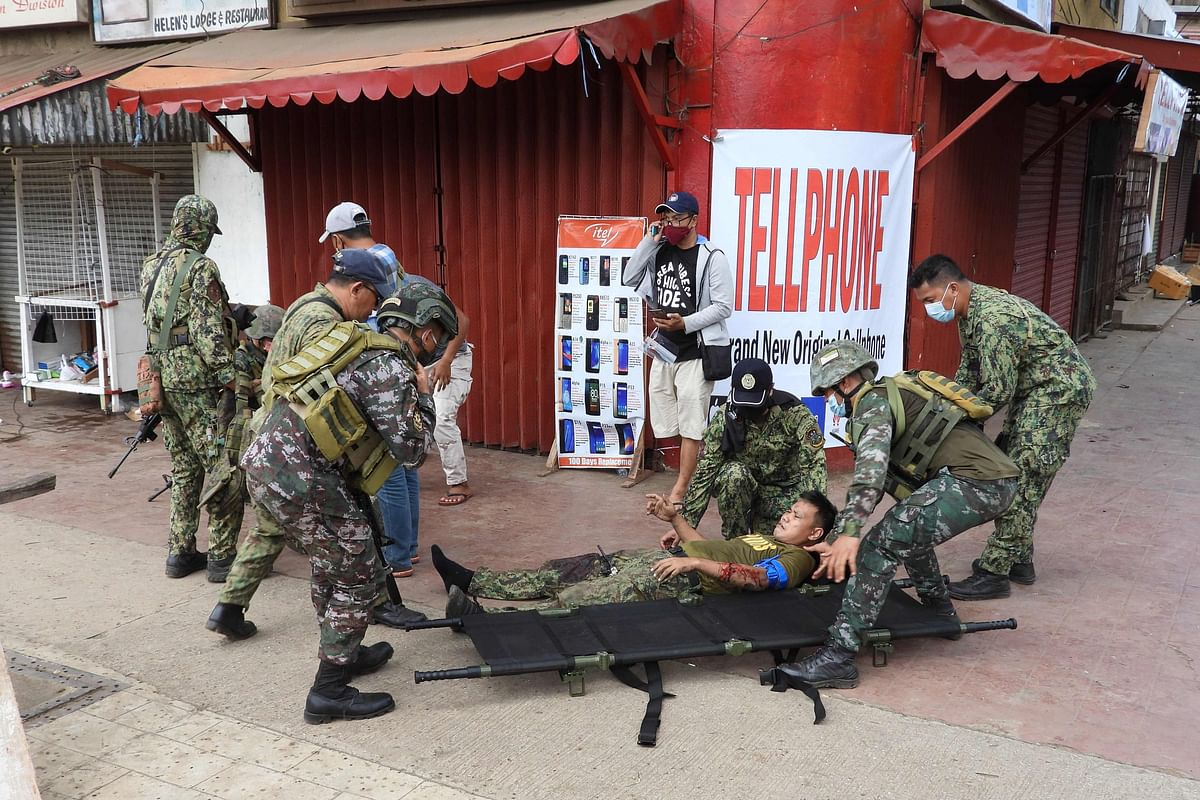 A wounded policeman is placed on a stretcher by colleagues at the scene of a bombing.