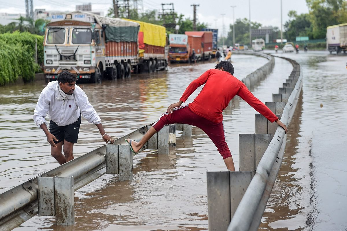 People cross a flooded road on a highway following monsoon rainfall in Gurugram on August 20, 2020.